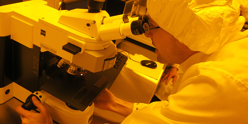 Graham Gibson peers through a microscope in the newly opened Kingston Nano-Fabrication Laboratory (KNFL). The unique colour is due to how light in the lab is filtered.