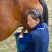 A Kyrgyz woman milks a horse.