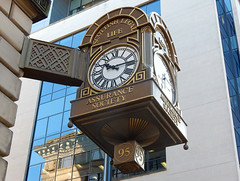 "An ornate, four-sided clock mounted just clear of the corner of a building.  The words ""Scottish Legal Life Assurance Society"" appear on each face, and a protrusion from the bottom carries the number 95."