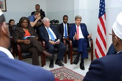 U.S. Secretary of State John Kerry, flanked to his left by U.S. Special Representative for Somalia James McAnulty and Assistant Secretary of State for African Affairs Linda Thomas-Greenfield, sits with President Hassan Sheikh Mohamud, Prime Minister Omar Abdirashid Ali Sharmarke, and three regional leaders - Abdiweli Gaas, Puntland President, Sharif Hassan, Interim South West Administration President, and Ahmed Madobe, Interim Juba Administration President - after arriving in Mogadishu, Somalia, on May 6, 2015, for a series of meetings with Somali government officials and civil society representatives. [State Department Photo/Public Domain]