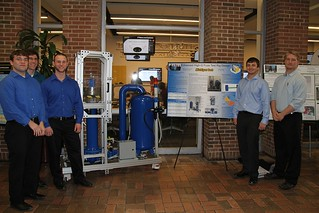Enhanced High-G Fuze Test Rig Design Team posing with poster and rig system