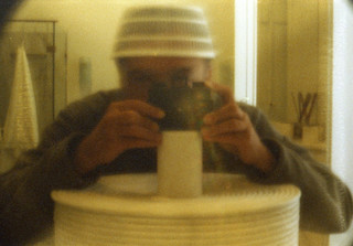 reflected self-portrait with Science Museum pinhole camera and ventilated hat