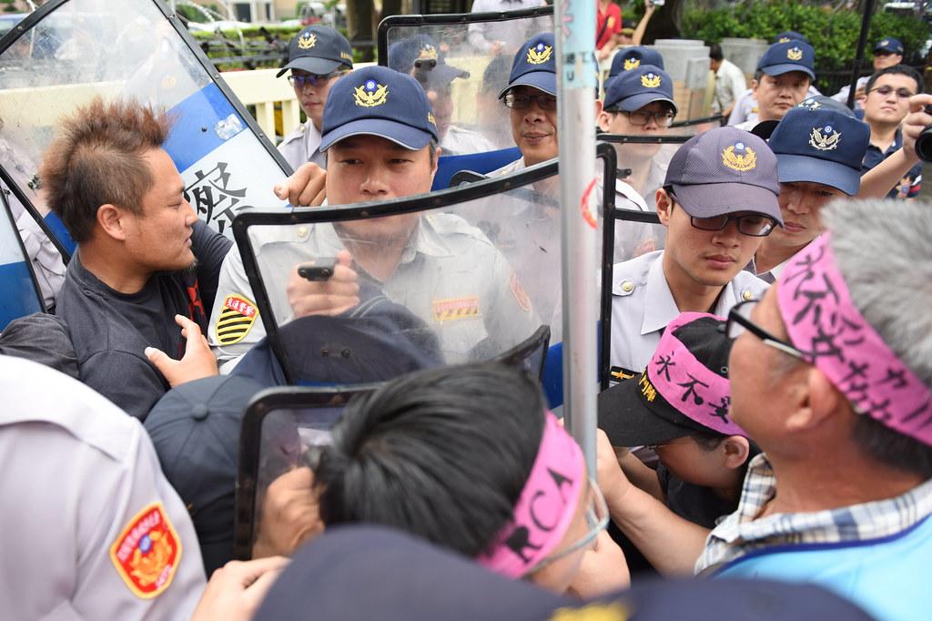 RCA工人及聲援者不滿行政院未回應訴求,一度激憤衝向大門與警方推擠。(攝影:宋小海)