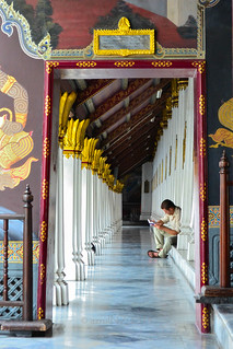 a visitor having his afternoon reading in one of the unique & amazing buildings of The Grand Palace, Bangkok