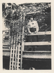 Woman stands next to a flowered-covered porch lattice 3