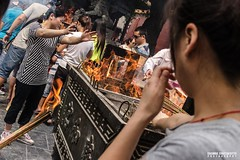 Faithful buddhist visitors light incense sticks from incense burner - Street photography