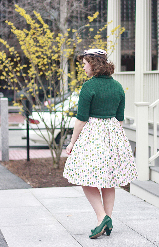Easter outfit with piano novelty print dress, green handknit sweater, green shoes, and pink and navy feathered hat
