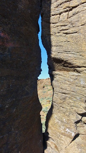 Image shows two basalt columns with a gap between. A wall of the coulee is visible through the gap.