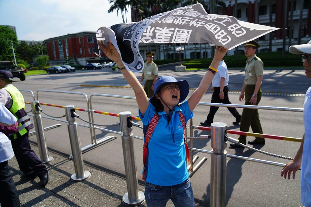 韓國全國金屬工會京畿道支部副部長嚴美野突襲總統府前拉開布條。(攝影:王顥中)
