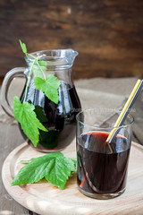 Glass and jug with fresh Black Currant juice decor…