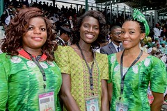 Three women in formal African dress smile after Goodluck Jonathan transferred power to Nigerian President Muhammadu Buhari during an inauguration ceremony - attended by U.S. Secretary of State John Kerry and other members of a delegation representing President Obama - at Eagle Square in Abuja, Nigeria, on May 29, 2015. [State Department photo/ Public Domain]