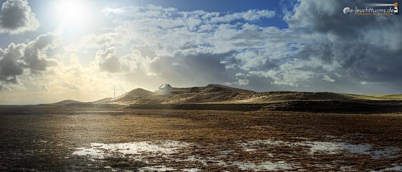 Lone house below Icelands sun