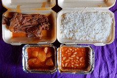 Two polystyrene boxes containing a large chunk of bone-in lamb and a large portion of white rice; and two foil trays containing a potato stew and a bean stew.  All is resting on a purple tablecloth.