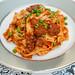 Homemade fettuccine, spicy Italian sausage, tomato sauce, peas