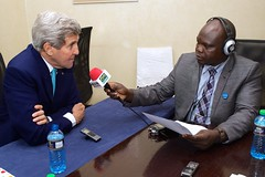 U.S. Secretary of State John Kerry sits for an interview with Nichola Mandil of Eye Radio after meeting with Kenyan government leaders, opposition leaders, representatives of the United Nations High Commissioner for Refugees, and Somali refugees in the Dadaab Refugee Camp while visiting Nairobi, Kenya, on May 4, 2015. [State Department Photo/Public Domain]