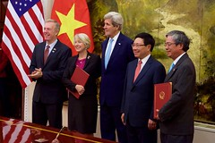 U.S. and Vietnamese officials -- including U.S. Ambassador to Vietnam Tes Osius, Peace Corps Director Carrie Hessler-Radelet, U.S. Secretary of State John Kerry, and Vietnamese Deputy Prime Minister and Foreign Minister Phạm Bình Minh -- pose for a photograph after the signing of a historic partnership to establish a Peace Corps program for the first time in Vietnam, at the Ministry of Foreign Affairs in Hanoi, Vietnam, May 24, 2016. The announcement of the partnership coincides with U.S. President Barack Obama's trip to Vietnam and underscores the United States' broader commitment to supporting the people of Vietnam through English language learning. [State Department photo/ Public Domain]