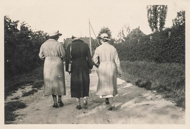 Women walking away down a sandy road