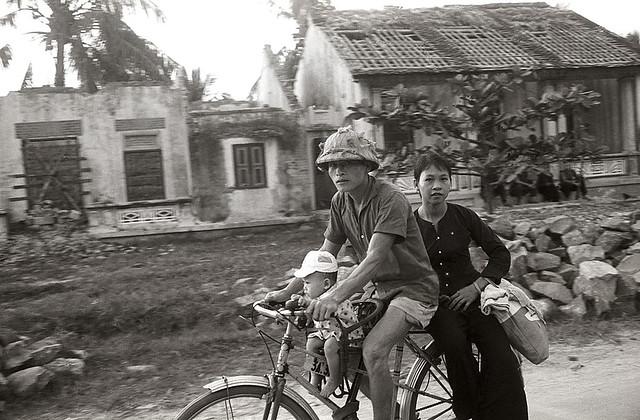 North Vietnam 1965 - Những người dân đi qua một ngôi làng đã bị Mỹ ném bom - Photo by Romano Cagnoni