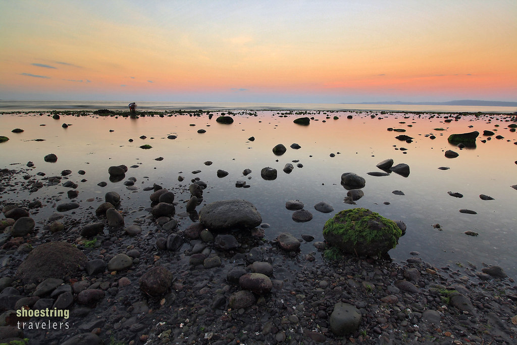 the rocky waterfront of Rizal Boulevard at sunset