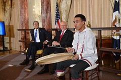 U.S. Secretary of State John Kerry and U.S. Special Representative for the Arctic Admiral Robert Papp look on as Byron Nicholai of Toksook Bay, Alaska performs a song in Yup'ik, a native Alaskan language, at the U.S. Chairmanship of the Arctic Council reception with  at the U.S. Department of State in Washington, DC on May 21, 2015. [State Department Photo/Public Domain]
