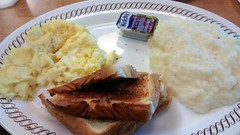 Scrambled Eggs, Toast, Grape Jelly And Grits.