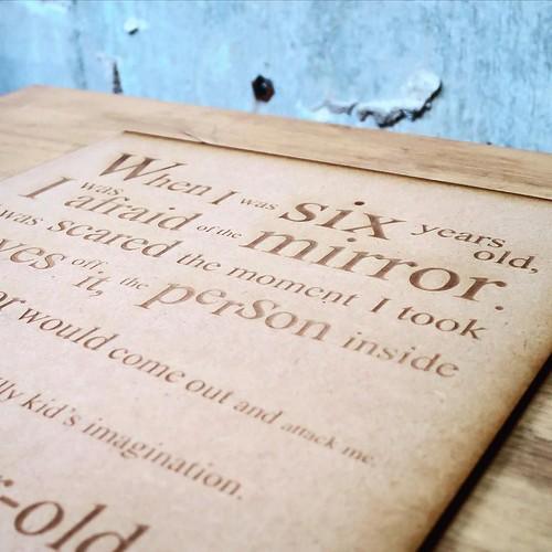 こちらが、本日メインの作品。クリエイティブ・ライティングのクラスで書いた小説の冒頭の文章をイラレでレイアウトして、レーザー加工機で板に彫る、と。