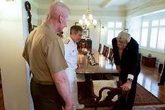 U.S. Navy Admiral Harry Harris, Commander of Pacific Command, joined by Lieutenant General John Toolan, U.S. Marine Corps Forces, Pacific, shows U.S. Secretary of State John Kerry the nameplates revealing the dignitaries who have sat at the dining room table in his quarters at Joint Base Pearl Harbor-Hickam, Hawaii, on May 25, 2016, a military briefing from Pacific Theater Combatant Commanders amid his travels back to Washington, D.C., from joining President Obama's trip to Vietnam. [State Department photo/ Public Domain]