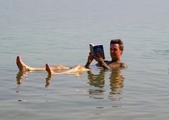 Floating in the Dead Sea and reading a book, Ein Bokek, Israel