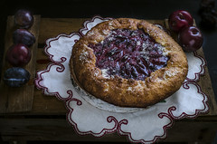 plum galette on dark background , selective focus