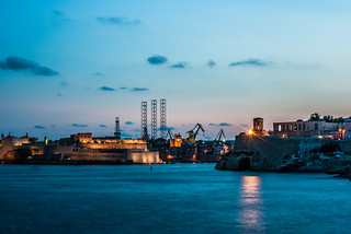 Image of  Fort Saint Angelo. malta breakwater blue sea grand harbor harbour oil rig fort st saint angelo fortifications bastions entrance night long expose dark light cranes ships lower barakka
