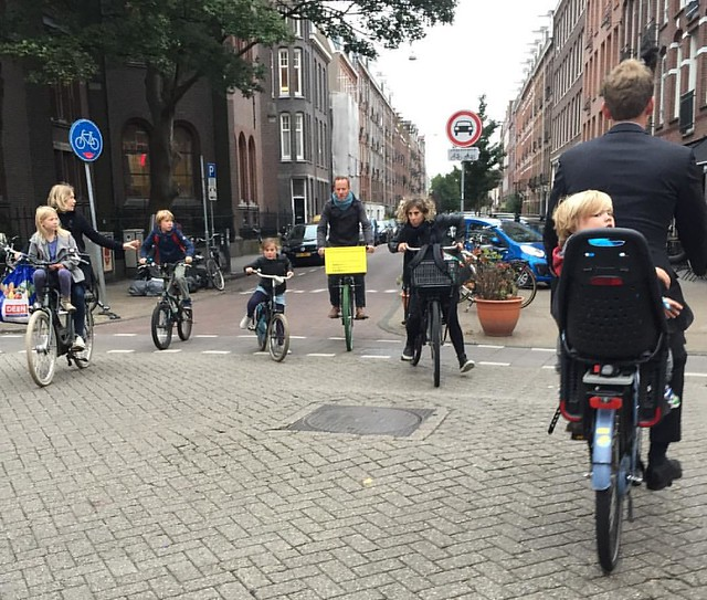Crossing the street #duthstyle during school drop off means 5 abreast, alert and relaxed, this way and that. And a little towhead eyeing the crazy lady with a camera.  #amsterdam #cyclechic #dutchlife #schoolkids #nofilter #streetlife @yeppbikeseats