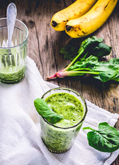 green smoothie with spinach leaves, banana with pe…