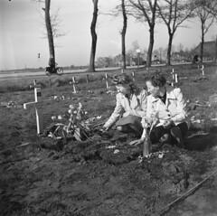 Twee meisjes verzorgen het tijdelijke graf van de Canadese soldaat H.W. Roszell die sneuvelde in de strijd om Groningen, 16 april 1945   Two girls at the temporary grave of the Canadien soldier H.W. Roszell who died in the battle of Groningen, april 16th