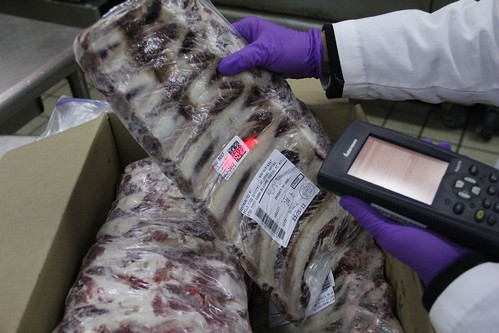A person scanning a meat product