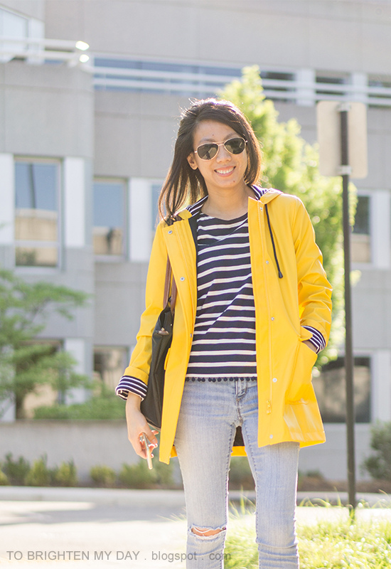 yellow rain jacket, striped top with pom poms, lightwash distressed jeans