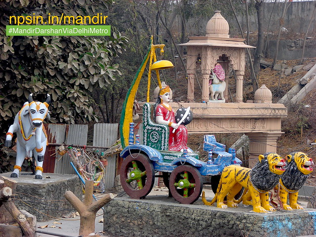 A symbolic representation of Bharat Maa riding on Rath having two lions. Also side view of Sherawali Maa gate from road side. With pure white bull shows the prosperity of country.