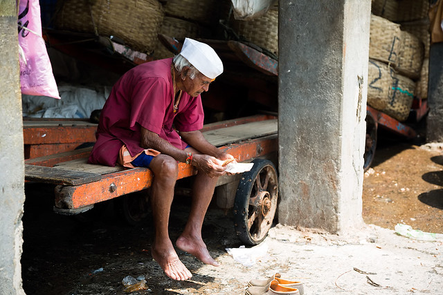 Man counting money at Sassoon Dock in Mumbai, India.