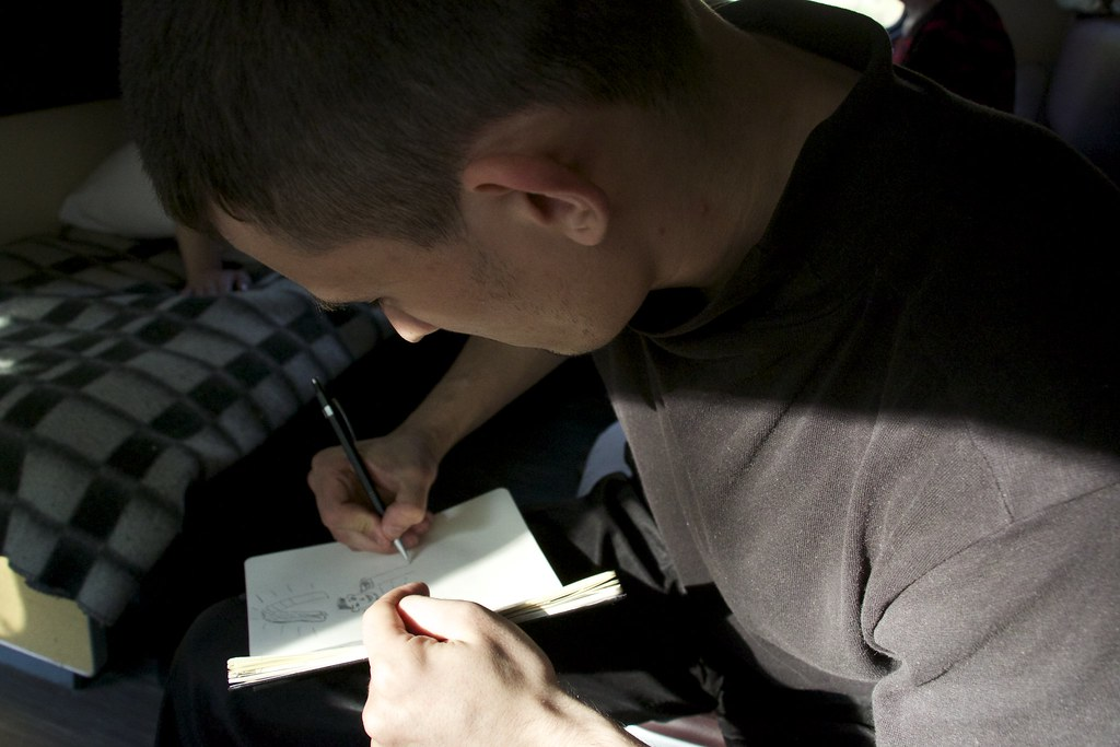Stas writing and drawing in our travel diary