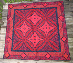 prayer rug(0.0), design(0.0), flooring(0.0), quilt(1.0), tapestry(1.0), art(1.0), symmetry(1.0), textile(1.0), red(1.0), quilting(1.0), carpet(1.0),