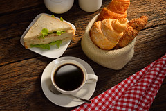 Coffee cup with sandwich and croissant.