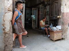 Shoemaker repairing shoes at the entrance of a building in Old Havana, Cuba