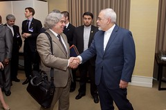 Iranian Foreign Minister Javad Zarif shakes hands with U.S. Energy Secretary Dr. Ernest Moniz as they arrive at a meeting room in Geneva, Switzerland, on May 30, 2015, for the latest round in the P5+1 negotiations about the future of Iran's nuclear program. [State Department Photo/ Public Domain]