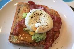 Smashed avocado on toast with poached egg and baco…