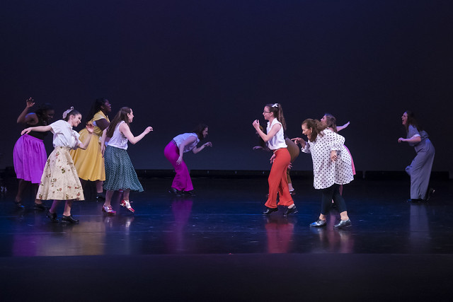 Ten dancers perform on stage during a production of