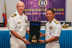 Capt. Randy Van Rossum, left, Pacific Partnership 2019 mission commander, receives a gift from Philippine Navy Rear Adm. Samuel Felix during the closing ceremony of the Philippines mission stop. (U.S. Navy/MC2 Nicholas Burgains)