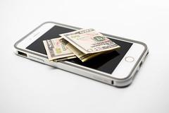 50 dollar bills over a phone