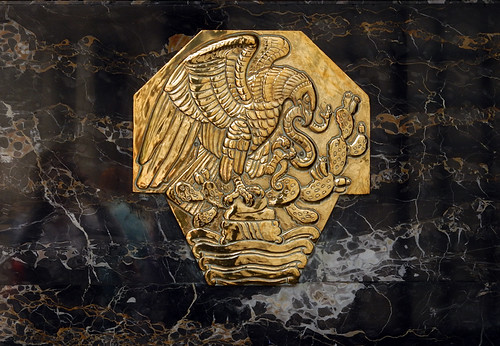 An eagle grasping a snake in its beak while sitting on a cactus, the symbol of Mexico, in a gold seal embedded in a black marble wall at the The Postal Palace, aka Palacio Postal, in Mexico City