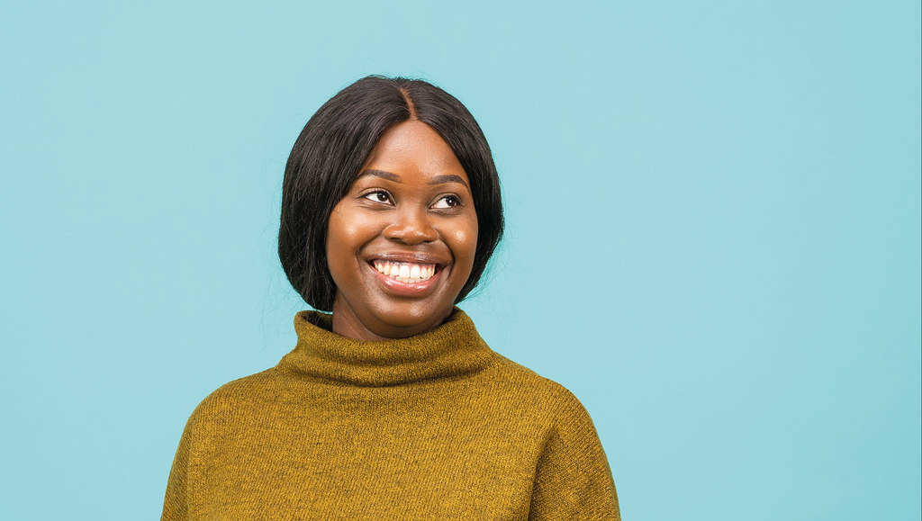 A photo of Taffy Mutamangira smiling in front of a blue background