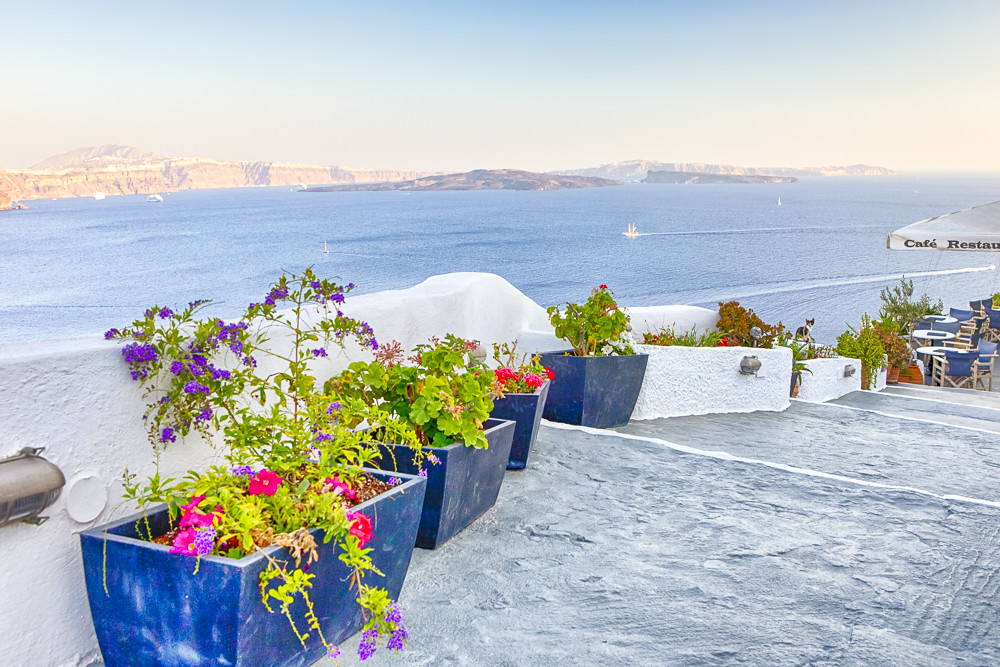 Travel Destinations.Picturesque Cityscape of Oia Village in Santorini with Volcanic Caldera and sailing Boats on Background.