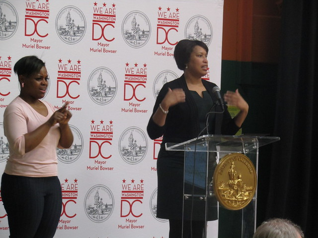 Photo of two women on stage near a podium with a